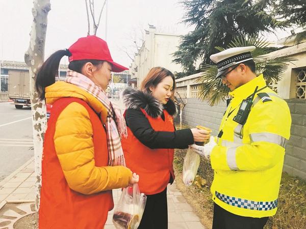 1月24日,望湖街道朱岗社区志愿者为正在路上执勤的交警同志送上腊八粥。(毛菡菁).jpg