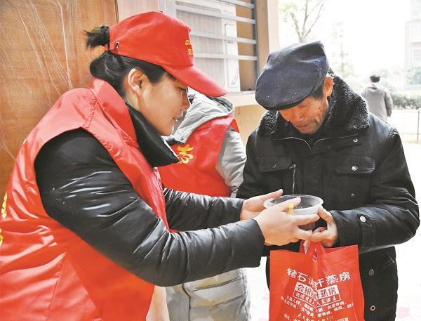 1月24日,天空中飘起了雪花,滨湖世纪社区的志愿者们抬着起早熬好的香浓腊八粥,在辖区小区的各主要出口处设立送粥点。.jpg